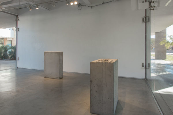 Lara Favaretto, <em>Boring</em>, 2010, Concrete, iron, 43 1/4 x 31 1/2 x 9 7/8 in (109.8 x 80 x 25 cm), and Lara Favaretto, <em>Fisting</em>, 2012 Concrete, iron, 39 1/8 x 17 1/4 x 29 1/4 in (99.4 x 43.8 x 74 cm), Glass Box Gallery, University California Santa Barbara, 2019, Courtesy MCASB, Photo: Brian Forrest.